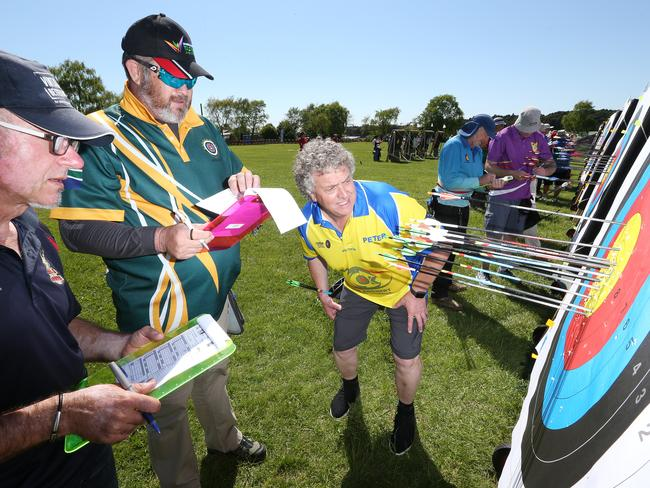From left, Tom Kawalski, of Eden Field Archers, Adelaide, Johann Viljoen, of Tuks Archery, South Africa, and Peter Carmichael, of Van Diemens Archers, Hobart, tally up the archery target scores.