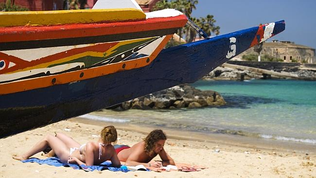 Sunbathers on beach besides a pirogue fishing boat.. Picture: Supplied