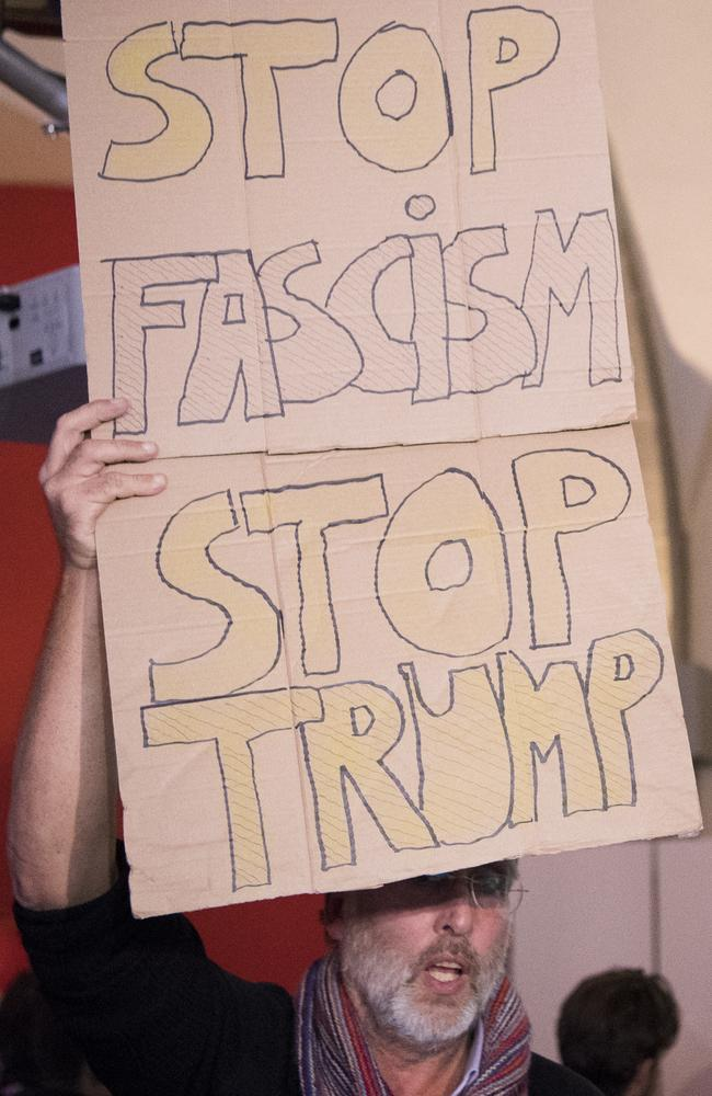 An anti-Trump protester in Switzerland carries a sign saying: 'STOP FASCISM STOP TRUMP'. Picture: Anthony Anex/Keystone via AP