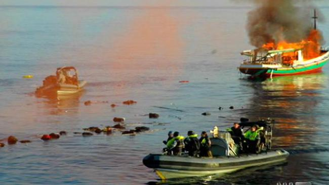 Defence sailors rescue asylum seekers as an asylum seeker boat catches fire and then explodes. Picture: Channel 9