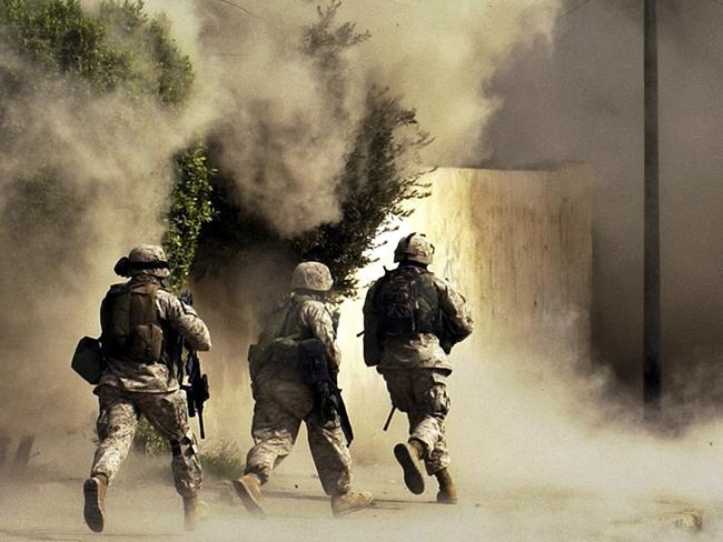 Warfare awaiting Australian Special Forces ... US Marines from the 2nd Battalion, 5th Marine Regiment, run to a building after detonating explosives to open a gate during a mission in Ramadi in Anbar province, Iraq. Picture: Jim MacMillan