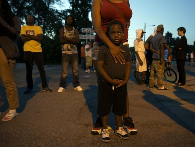 Witness ... Jeremiah Parker, 4, stands in front of his mother, Shatara Parker, as they attend a protest in Ferguson. Nights of unrest have vied with calls for calm in a St. Louis suburb where Michael Brown, an unarmed black teenager was killed by police, while the community is still pressing for answers about the weekend shooting. Picture: AP
