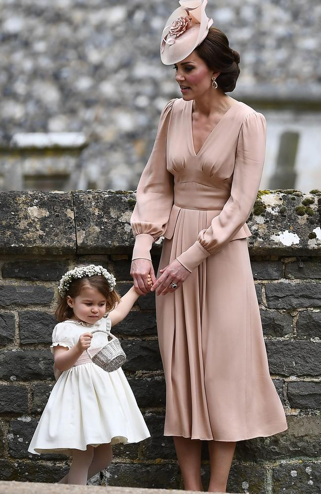 The duchess waits patiently with her daughter following Pippa's ceremony.