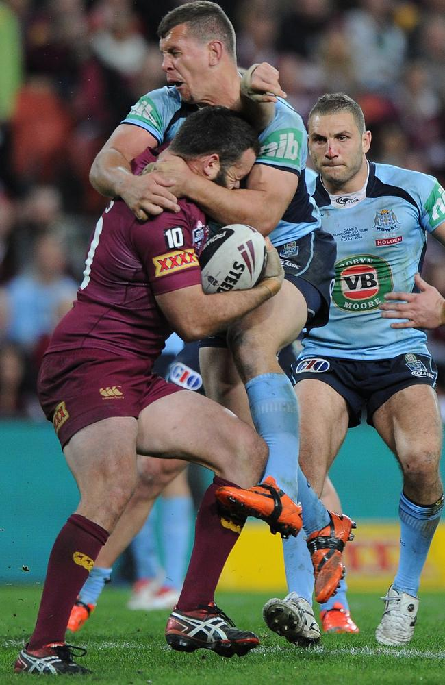 Nate Myles of the Maroons is tackled by Greg Bird of the Blues.