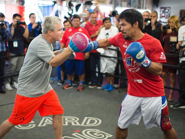 Pacquiao hits the pads with Roach.