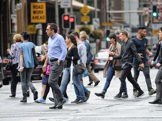 Sydney, Australia - November 5, 2015: Diversified people crowd crossing rain wet street. Scene from central Sydney.
