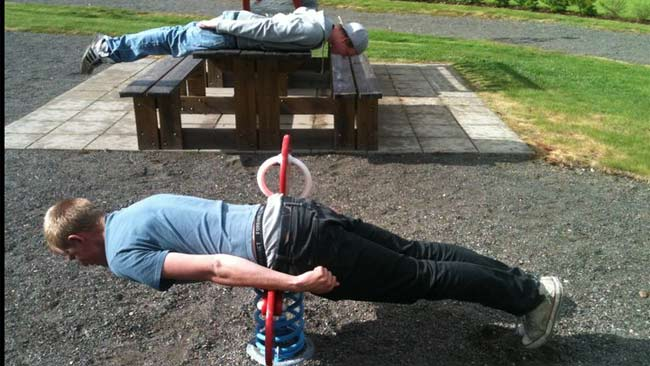 Two men plank in a childrens' playground. Picture: Facebook