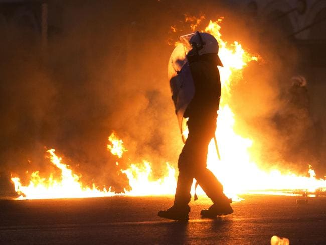 A riot policeman, framed by fire.