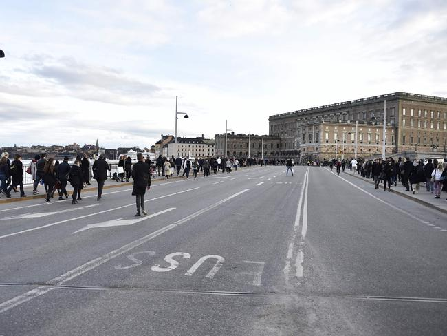 People walk through Stockholm after public transport was shut down following the 'terror attack'.