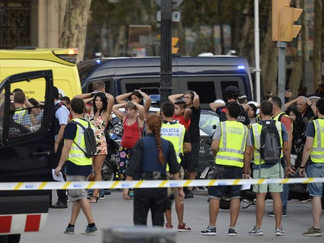 Policemen check the identity of people standing with their hands up after a van ploughed into the crowd. Picture: AFP