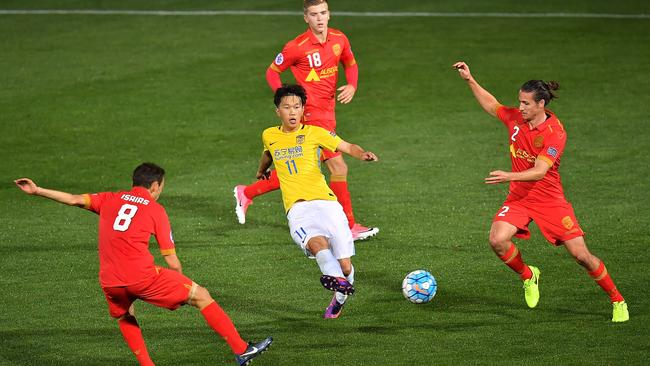 Xie Pengfei finds space among the Adelaide players. (Photo by Daniel Kalisz/Getty Images)