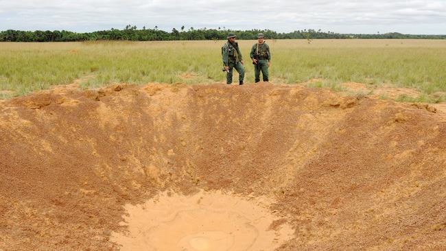 Venezuelan National Guard soldiers by a crater exploded into a clandestine drug airstrip in Apure. Picture: Leo Ramirez