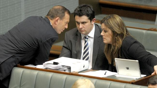 Opposition Leader Tony Abbott speaks to advisers Andrew Hirst and Peta Credlin in 2013. Picture: AAP/Alan Porritt
