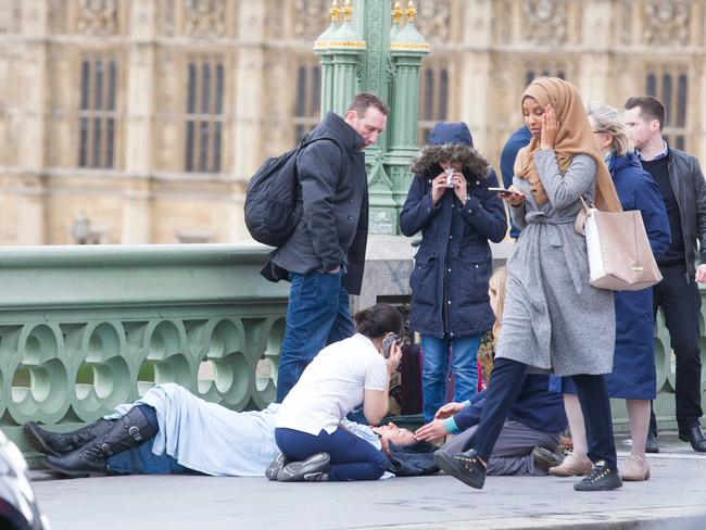 This picture of a Muslim woman walking past one of the injured has drawn criticism online. It is not known if she had been helping victims prior to this shot being taken. Picture: REX/Shutterstock/australscope