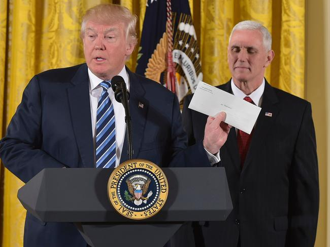 US President Donald Trump holds the letter left for him by former US President Barack Obama, as Vice President Mike Pence watches, before the swearing in of White House senior staff on January 22, 2017. Picture: AFP/Mandel Ngan