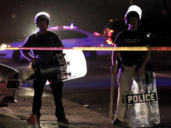 On guard ... Police wearing riot gear stand at a post as they wait for a crowd to disperse in Ferguson. Source: AP