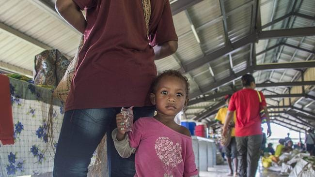 A young girl with her mother at the new central market at Lorengau.