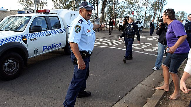 Locals shout abuse as a police van carrying Kiesha Abrahams' mother and stepfather is driven past them / Picture: Daily Telegraph