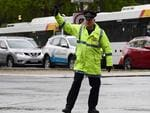 Sen-Constable Brian Strathearn directs traffic on North Tce and King William St. Picture: Campbell Brodie