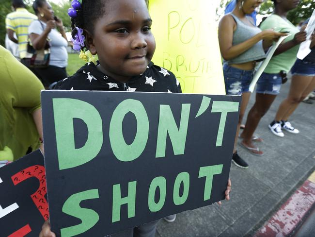 "Occupied territory ... Jaerina Willis, 7, holds a sign that reads ""Don't Shoot"" as she attends an evening rally in support for protesters in Ferguson, Missouri., where the fatal shooting of 18-year-old Michael Brown has sparked nightly clashes between protesters and police. Source: AP"