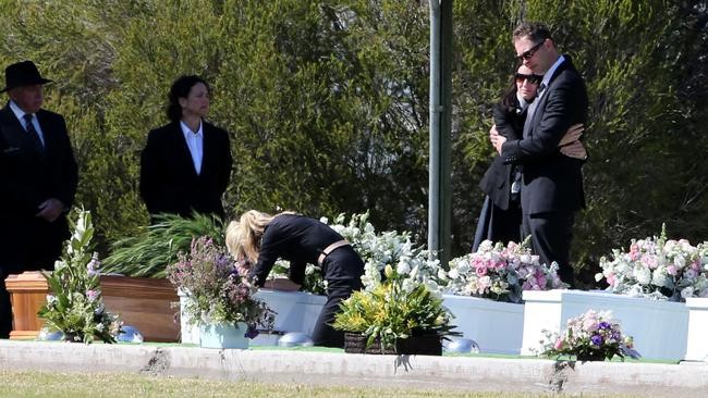 Jenny Geppert bows over the coffin of her sister Kim Hunt among those of Geoff Hunt and their three children that he murdered in 2014.