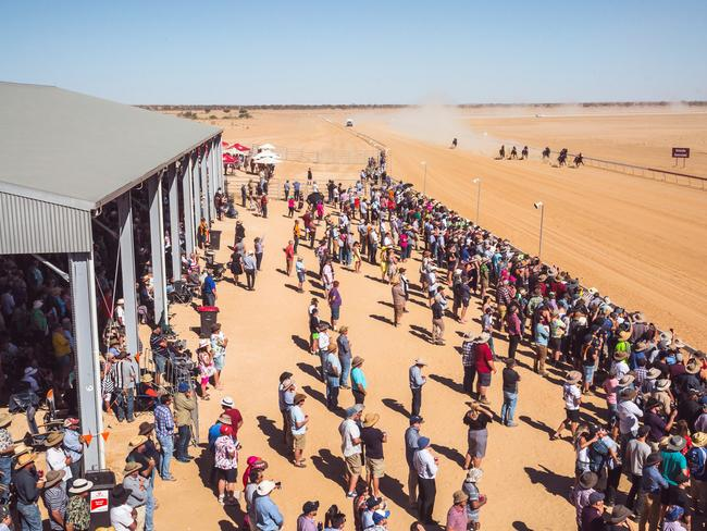 The horses thunder down the home strait at the Birdsville racetrack.