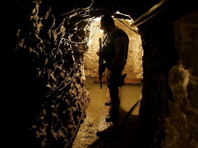 Police agent with US Immigration and Customs Enforcement stands guard in a drug tunnel found along the Mexico/USA Border at a warehouse January 30, 2006 in Otay Mesa, California.