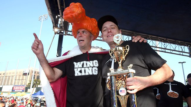 Competitive eater Joey Chestnut, right, stands with the Wing King Drew Cerza after eating a record 191 chicken wings in 12 minutes. Picture: AP Photo/The Buffalo News, Robert Kirkham.