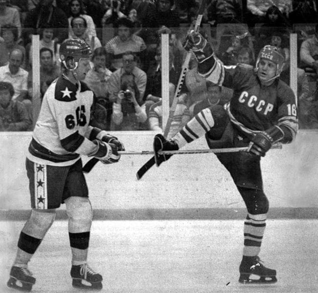 Bill Baker (left) attempts to remove his stick stuck through hole in the skate of opponent Vladimir Petrov during USA v USSR match at the 1980 Lake Placid Winter Olympic Games.