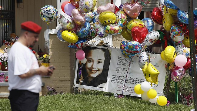 Cleveland's House of Horrors: a Guardian Angel waits for the car carrying kidnap victim Gina DeJesus to arrive at her house in Cleveland, Ohio. DeJesus was one of three women who were held captive for almost a decade by Ariel Castro, who has been charged with kidnap and rape. Photo: Matt Sullivan/AFP