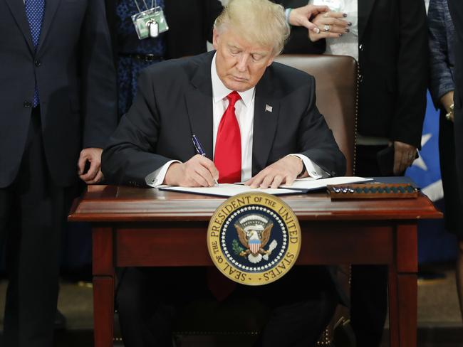 "President Donald Trump signs an executive order with a signature that shows no soft curves, but ""bigheadedness, anger and fear"" experts say. Picture: AP/Martinez Monsivais."