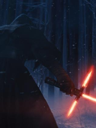 Adam Driver as Kylo Ren with his lightsaber.