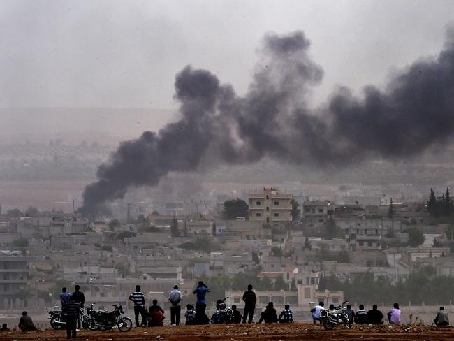 Battleground ... Kurdish people look at smoke rising from the Syrian town of Kobane after Kurdish fighters halted a thrust by Islamic State group jihadists towards the heart of the town. Picture: AFP / ARIS MESSINIS