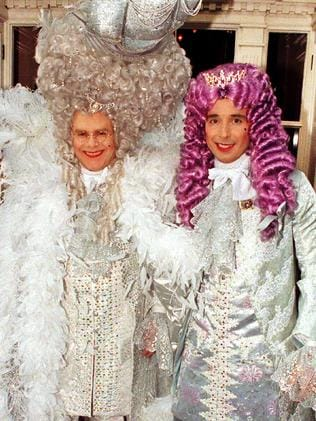 Elton's 50th ... Elton John (l) wearing silver costume, wig and train of ostrich feathers with David Furnish (r) leaving their London home. Picture: Supplied