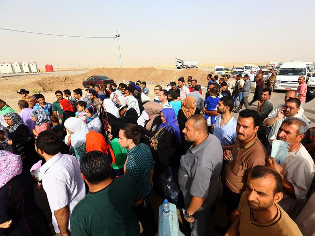 Fleeing Sharia rule ... Refugees from Mosul head to the self-ruled northern Kurdish region in Irbil, Iraq. An estimated half a million residents fled the economic centre of Mosul after it fell to rebels on Tuesday.