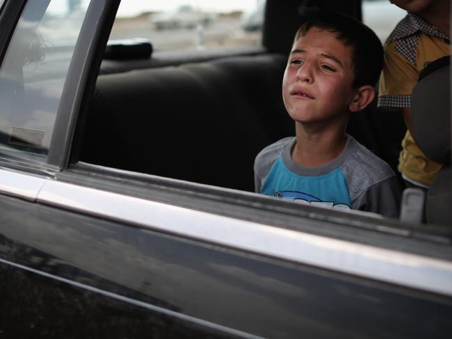 A boy cries for reasons unknown while waiting in a car at a Kurdish checkpoint in Kalak, Iraq. Picture: Dan Kitwood/Getty
