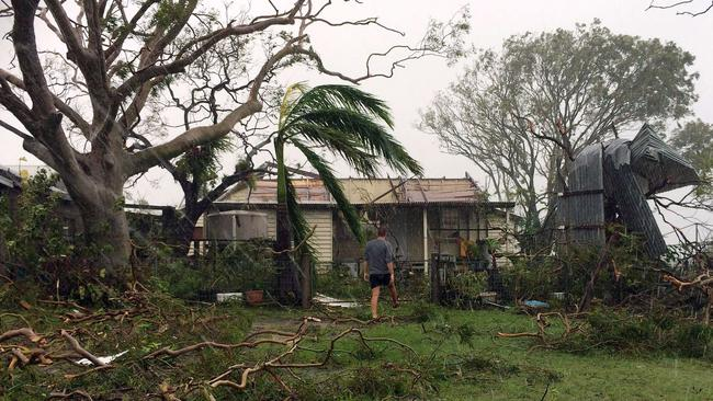 A man enters into a badly damaged house after Tropical Cyclone Marcia hit the coastal town of Yeppoon in north Queensland on February 20, 2015. AFP PHOTO / SHELLY ALLSOP