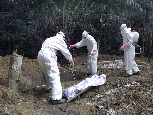 Workers wearing protective clothing bury five-year old Adamou, next to the graves of other Ebola victims.