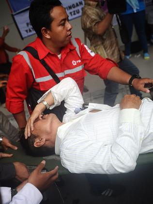A relative receives medical attention as he collapses at the breaking news. Picture: Robertus Pudyanto