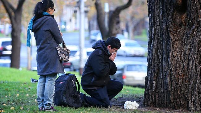 A young couple leave flowers near the police memorial. Picture: Mark Stewart