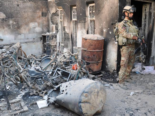 Deadly attack ... a member of the Iraqi security forces stands outside a burnt house in the city of Ramadi, west of Baghdad. Picture: Azhar Shallal