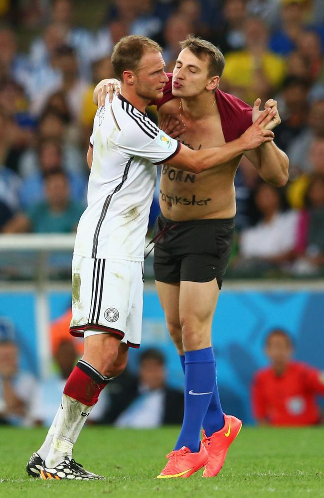 A pitch invader tries to kiss Benedikt Hoewedes of Germany during the 2014 FIFA World Cup final.