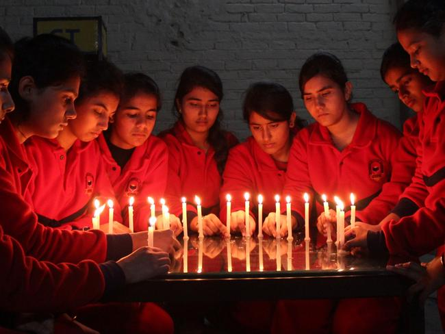 Bound in grief ... Indian schoolchildren prepare lit candles ahead of a vigil in the northern city of Jalandhar as they pay tribute to the slain Pakistani schoolchildren and staff. Picture: AFP PHOTO/SHAMMI MEHRA