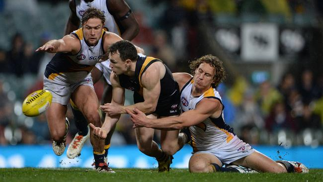 Eagle Matt Priddis tires to stop Nathan Foley dishing off a handball. Picture: Daniel Wilkins