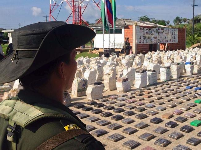 A Colombian police officer stands guard over more than seven tonnes of seized cocaine. Picture: AFP/ Policia Nacional handout