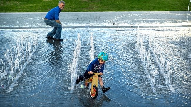 Bennett Fitzgerrald, 4, and his Dad Luke enjoy the Victoria Square fountains. Picture: Mike Burton.