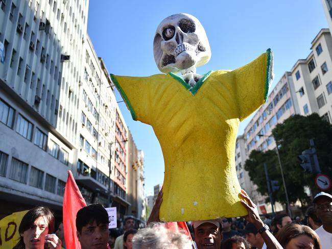 Demonstrators holding an effigy with a skull head in the colours of a Brazilian football shirt.