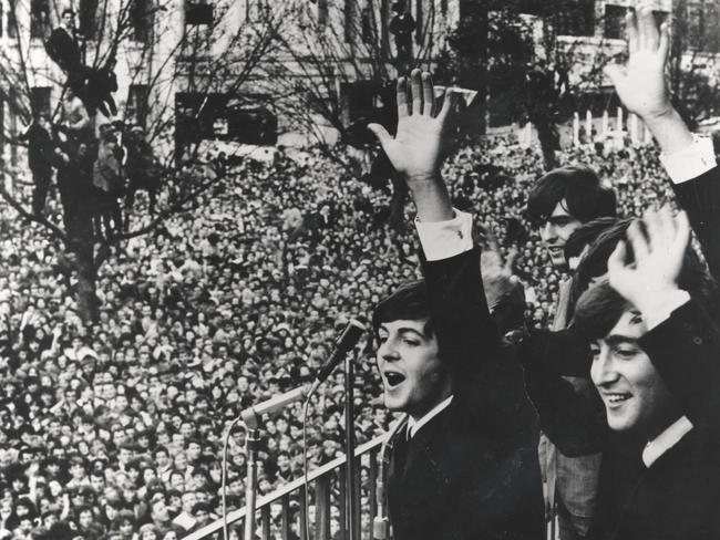 Greeting their Australian fans ... The Beatles wave to unprecedented crowds outside the Southern Cross Hotel in Melbourne. Picture: Supplied