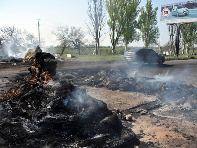 Aftermath ... a checkpoint of Pro-Russian militants smoulders after it was burned during an anti-terrorist operation by Ukrainian troops near the village of Kostyantynivka.
