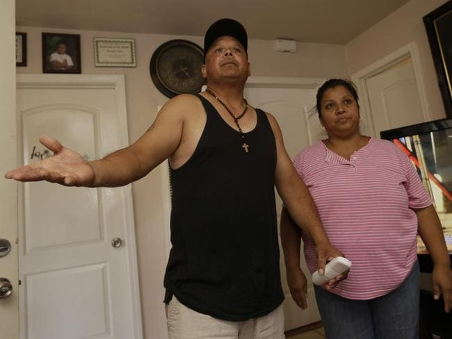 In shock ... Neighbours Ernesto Rios, left, and wife, Lourdes Hernandez express their disbelieve on the charges against Isidro Garcia. Picture: Damian Dovarganes